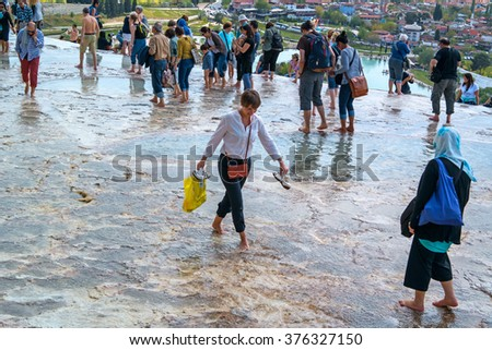 Pamukkale, Turkey - April 26, 2015: Tourists walk on the water flowing from the travertine terraces. In the foreground smiling girl in a good mood.