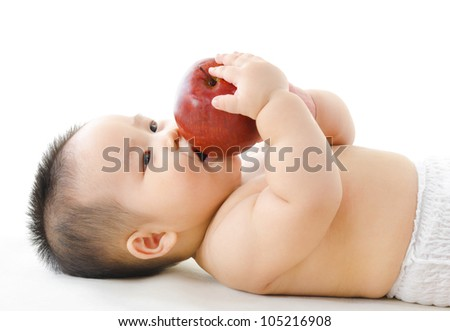 Pan Asian baby boy eating red apple on bed - stock photo