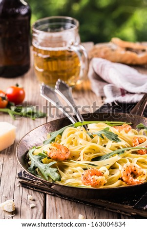 Pan fried italian pasta with shrimps and rucola. - stock photo