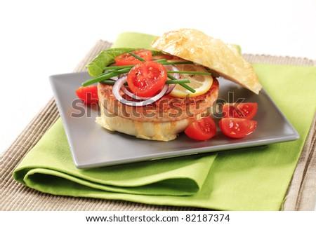 Pan fried salmon patty in cheese-topped bun - stock photo