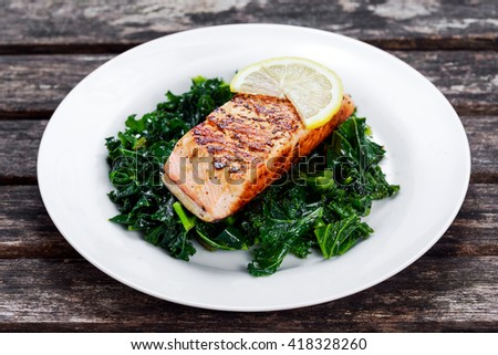 Pan fried Salmon Served with Kale on plate - stock photo