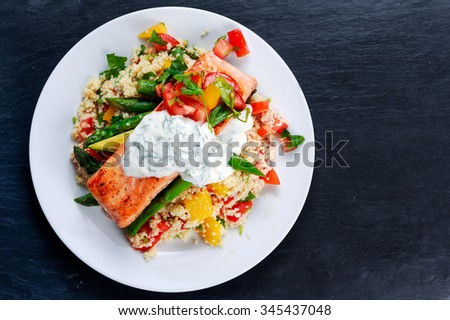 Pan fried Salmon with tender asparagus, courgette served on couscous mixed with sweet tomato, yellow pepper, greek yogurt with Dill on old blue stone background. - stock photo