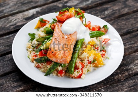 Pan fried Salmon with tender asparagus, courgette served on couscous mixed with sweet tomato, yellow pepper, with greek yogurt on old wooden table. - stock photo