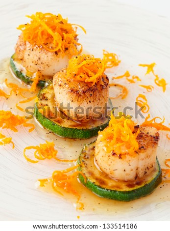 Pan fried scallops with citrus zest close-up