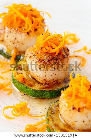 Pan fried scallops with citrus zest on plate, close-up - stock photo