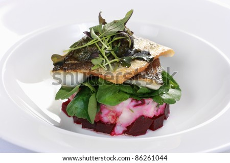 Pan-fried sea bass on a bed of crushed potato and beetroot with watercress salad - stock photo