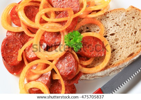 Pan fried slices of spicy sausage with onion and bread