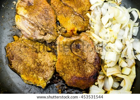Pan fried steak fillet with onions flat lay top view perspective isolated on black background - stock photo