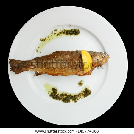 Pan fried trout on plate, isolated in black background - stock photo