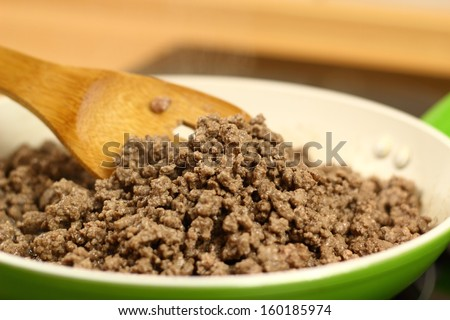 Pan frying ground beef. Making enchilada tortilla with beef.  - stock photo