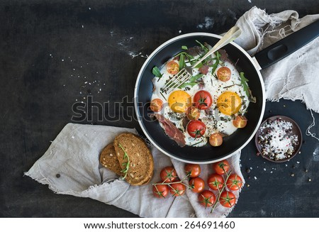 Pan of fried eggs, bacon and cherry-tomatoes with bread on dark table surface, top view - stock photo
