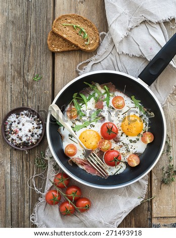 Pan of fried eggs, bacon and cherry-tomatoes with bread on rustic wood table surface, top view. - stock photo