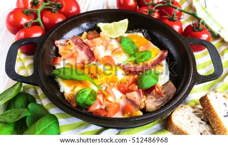 Pan of scrumbled fried eggs with tomatoes, bacon, spinach and lime with pieces of bread. Breakfast