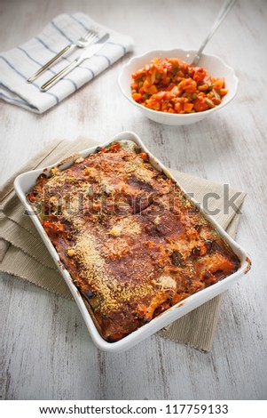 Pan of vegetarian lasagne and bowl with veggies