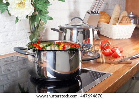 pan on the stove with vegetables in kitchen interior home - stock photo