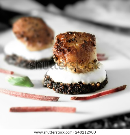 Pan seared scallops on a black pudding with creme fresche and beetroot salad garnish. - stock photo