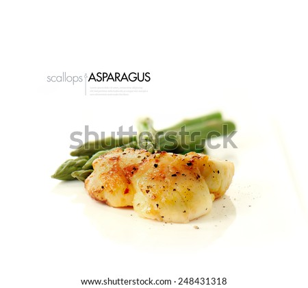 Pan seared scallops with fresh steamed asparagus against a white background. Copy space. - stock photo