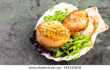 Pan seared scallops with garnish on a stone plate..