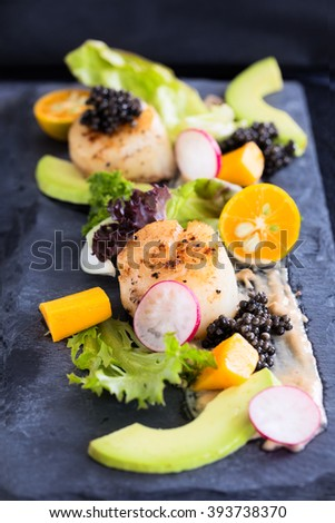 Pan seared scallops with salad, avocado, radish, mango and black caviar on a stone plate, vertical composition - stock photo