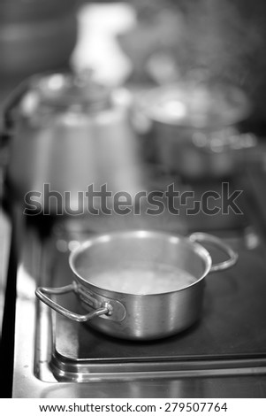 Pan with boiling water on a stove - stock photo