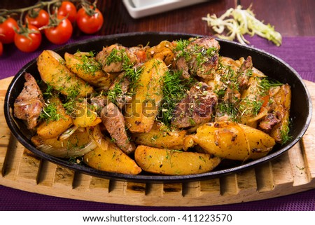 pan with fresh hot meat,potatoes and green dill in restaurant