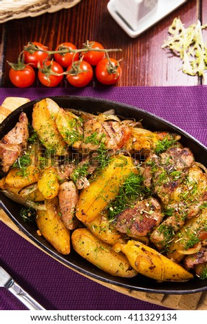 pan with fresh hot meat,potatoes and green dill in restaurant - stock photo