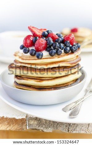 Pan with pancakes, blueberries and strawberries and cup of coffee