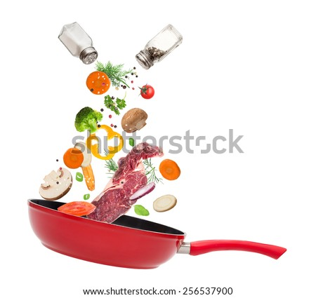 Pan with vegetables in freeze motion isolated on white background. - stock photo