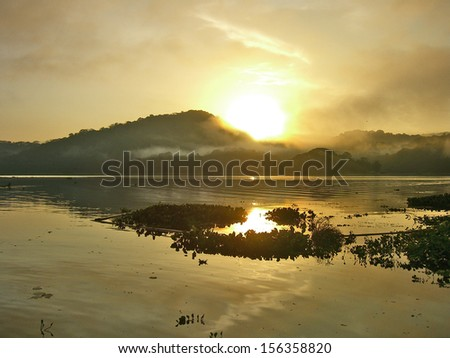 PANAMA CHANNEL AREA, PANAMA, DECEMBER 8 2006. A beautiful sunrise in the Panama Channel, with the morning fog, on December 18th 2006.  - stock photo