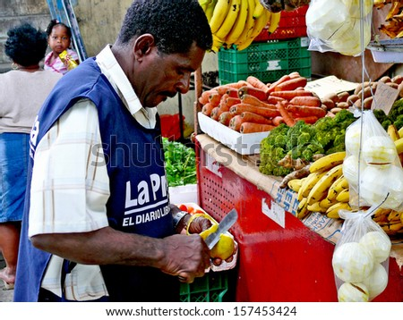 PANAMA CITY, PANAMA, DECEMBER 20 2006.  A coloured man peeling a fruit in front of a fruit selling stand, in Panama City, on December 20th 2006. FOR EDITORIAL USE ONLY. - stock photo