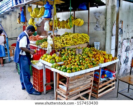 PANAMA CITY, PANAMA, DECEMBER 20 2006.  A coloured man peeling a fruit in front of a fruit selling stand, in Panama City, on December 20th 2006. FOR EDITORIAL USE ONLY.