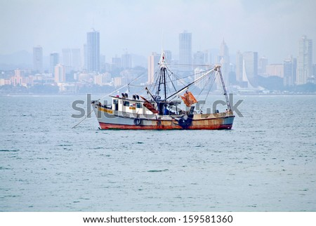 PANAMA CITY, PANAMA, DECEMBER 20 2006. A ship in the sea with skyscrapers in the horizon, in Panama City, on December 20th 2006. - stock photo