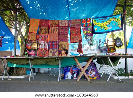 PANAMA CITY, PANAMA - JANUARY 18, 2014: A Kuna woman selling molas in an open air market in Panama City. The Kuna people, also known as Guna, are indigenous people of Panama and Colombia.  - stock photo