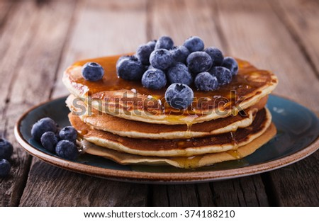 Pancake folded stack of with liquid honey and fresh blueberries on wooden background.selective focus. - stock photo