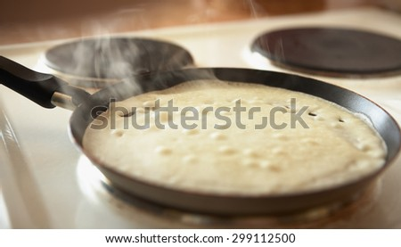 pancake fried in a pan with handle. Steam rises - stock photo