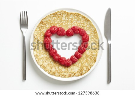 Pancake on plate with love heart shape cut out on white table