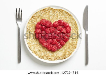 Pancake on plate with love heart shape on table - stock photo