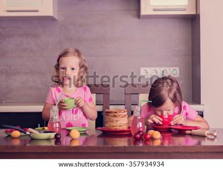 Pancake week. Little girls (sisters) eat pancakes. Selective focus. - stock photo