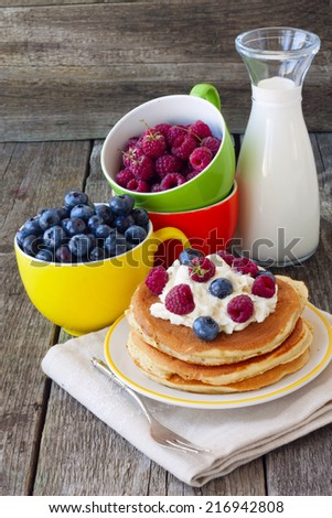 Pancake with curd and fresh berries and a bottle of milk