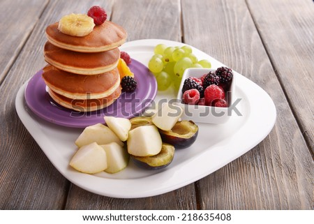 Pancake with fruits and berries on plate on wooden table