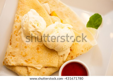 Pancake with ice cream and strawberry sauce on restaurant table