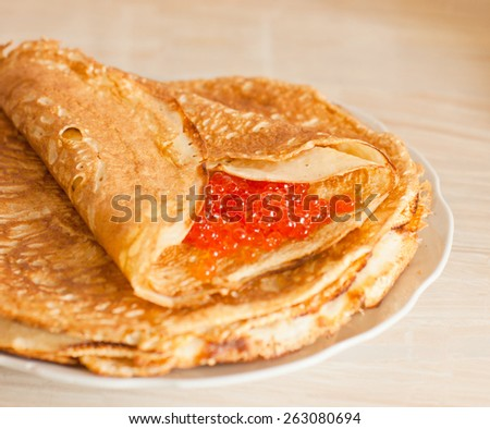 Pancake with red caviar on table. Traditional Russian cuisine
