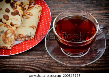 Pancakes and a cup of tea on wooden background - stock photo