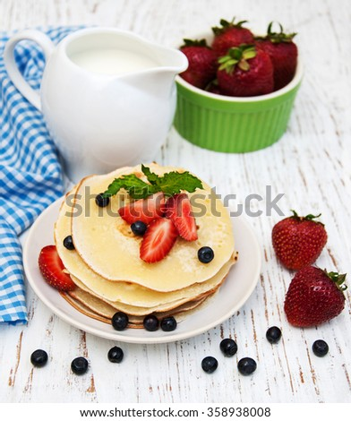 pancakes and fresh berries on a old wooden background