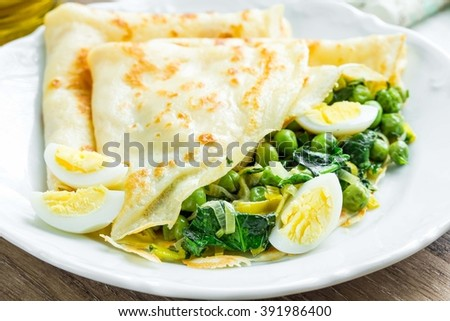 Pancakes, crepes stuffed with green peas, spinach, leeks, Russian Shrovetide, tasty dish
