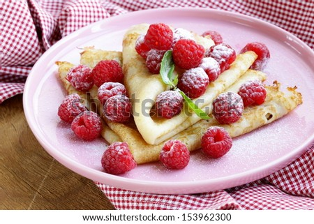 pancakes (crepes) with raspberries and mint -  healthy breakfast - stock photo