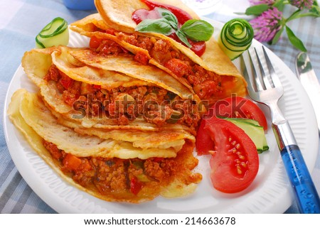 pancakes filled with minced meat and vegetables in tomato sauce