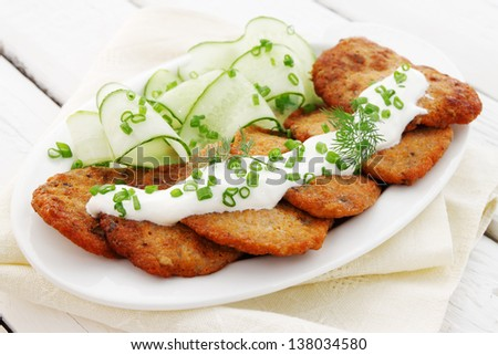 Pancakes from caviar carp with sour cream and cucumber