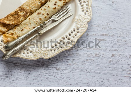 Pancakes in plate with fork and knife