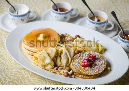 Pancakes in the range of honey , jam , cream and berries. Sweets on Shrovetide , the holiday before Easter. Close-up on a white plate.